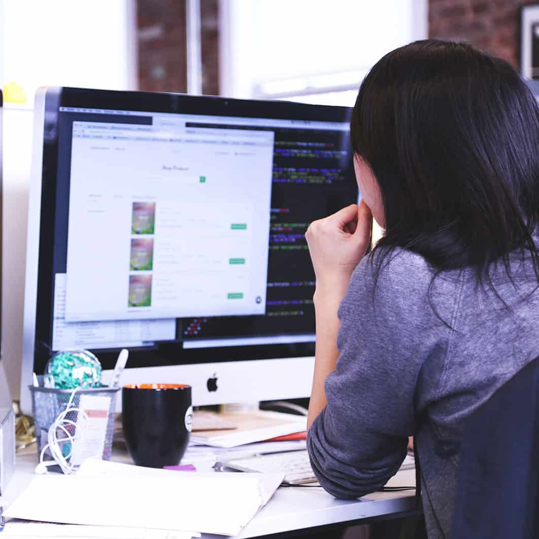 a girl programmer coding an eCommerce website using apple iMac.
